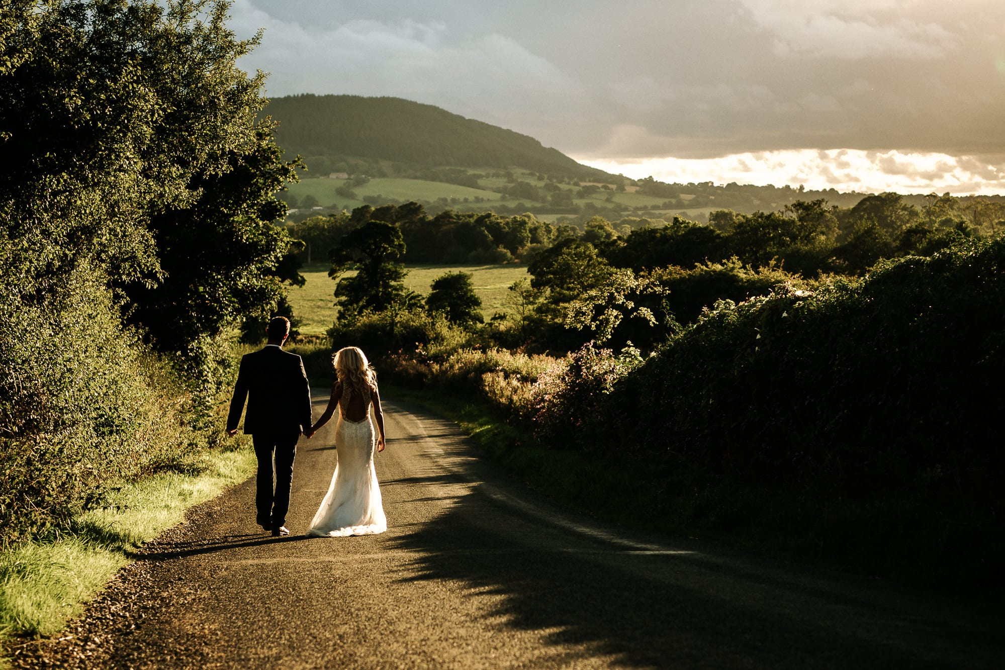 Bride and groom walking down the road with sunset