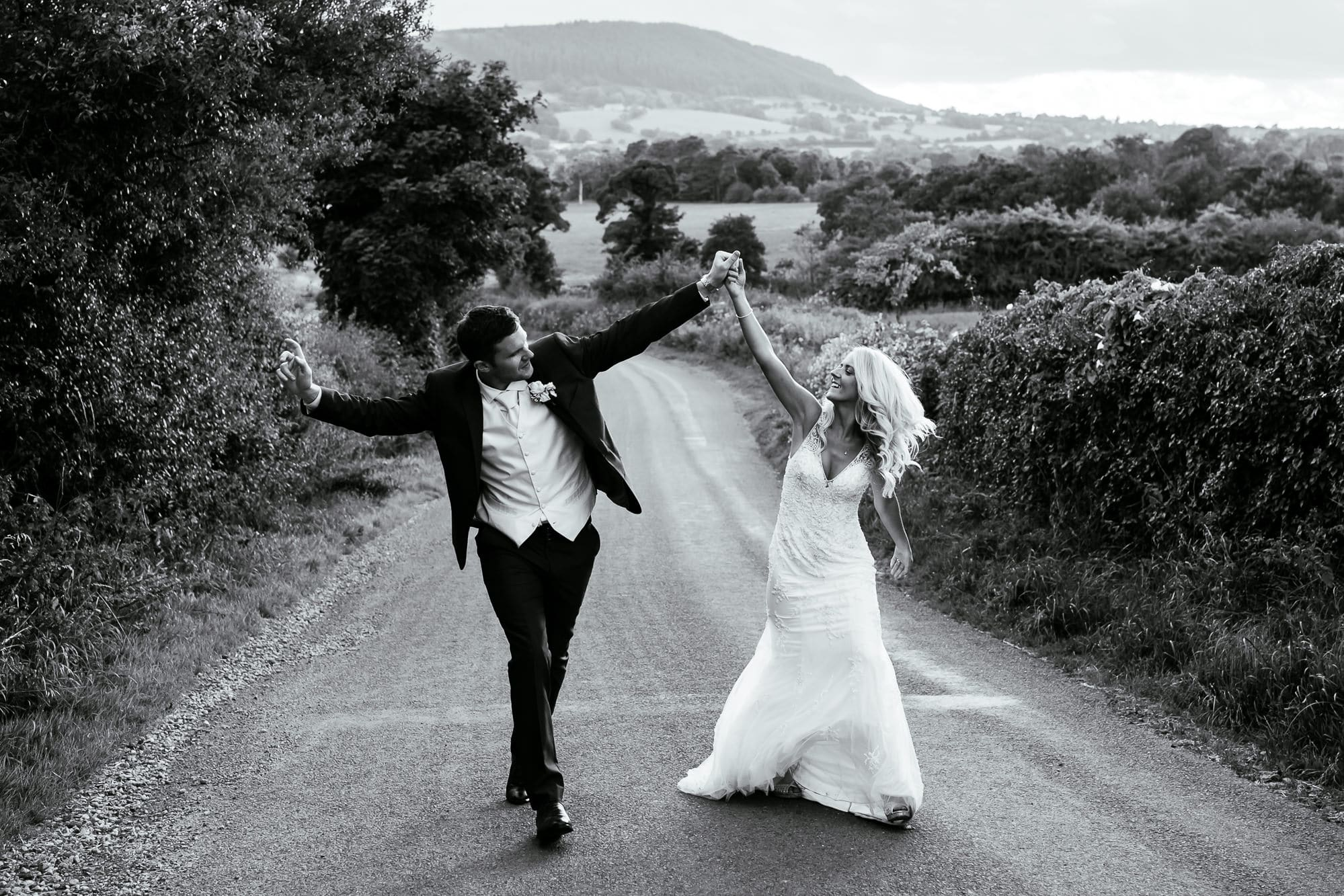 Bride and groom walking down the road at Bashall Barn