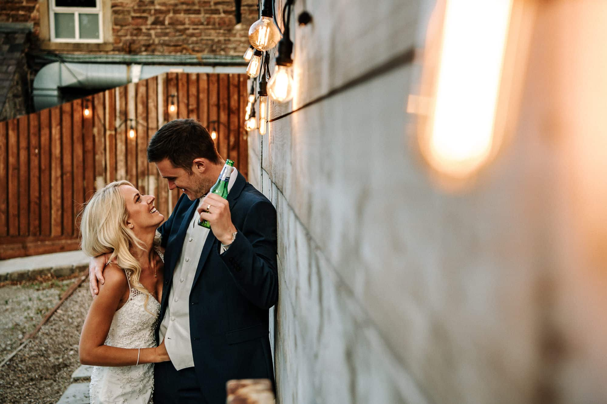Bride and groom cuddling against a wall at Bashall Barn