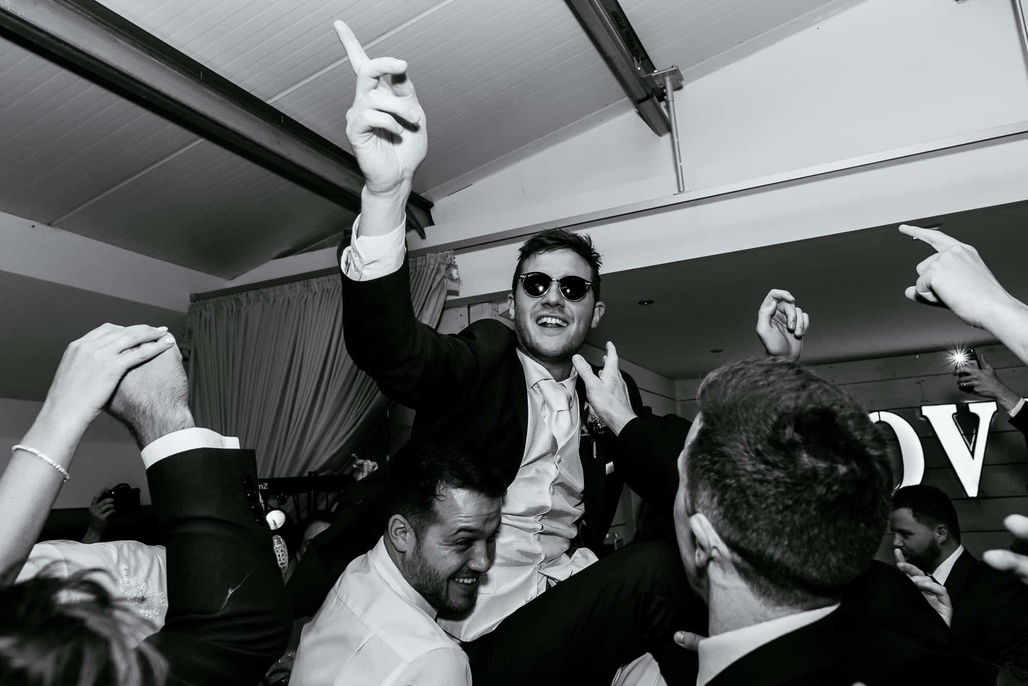 Groom on the dance floor on guests shoulders