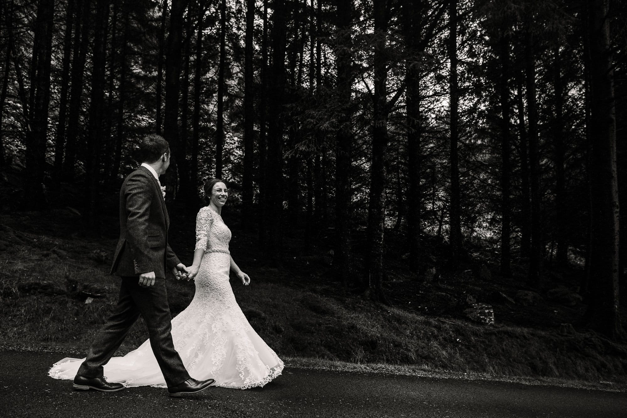 Bride and groom walking by trees in Nant Gwrtheyrn