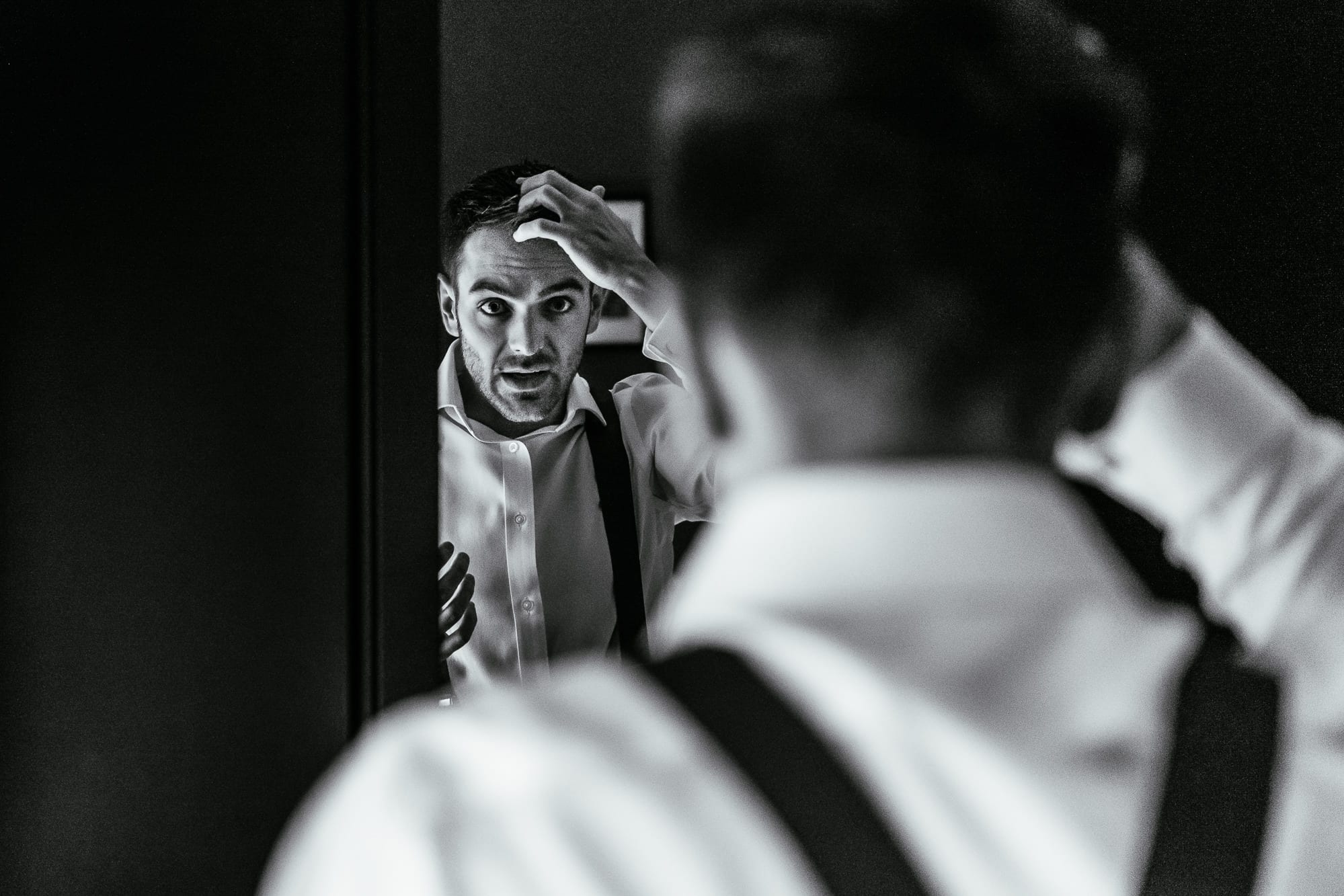 groom doing his hair before leaving for the church