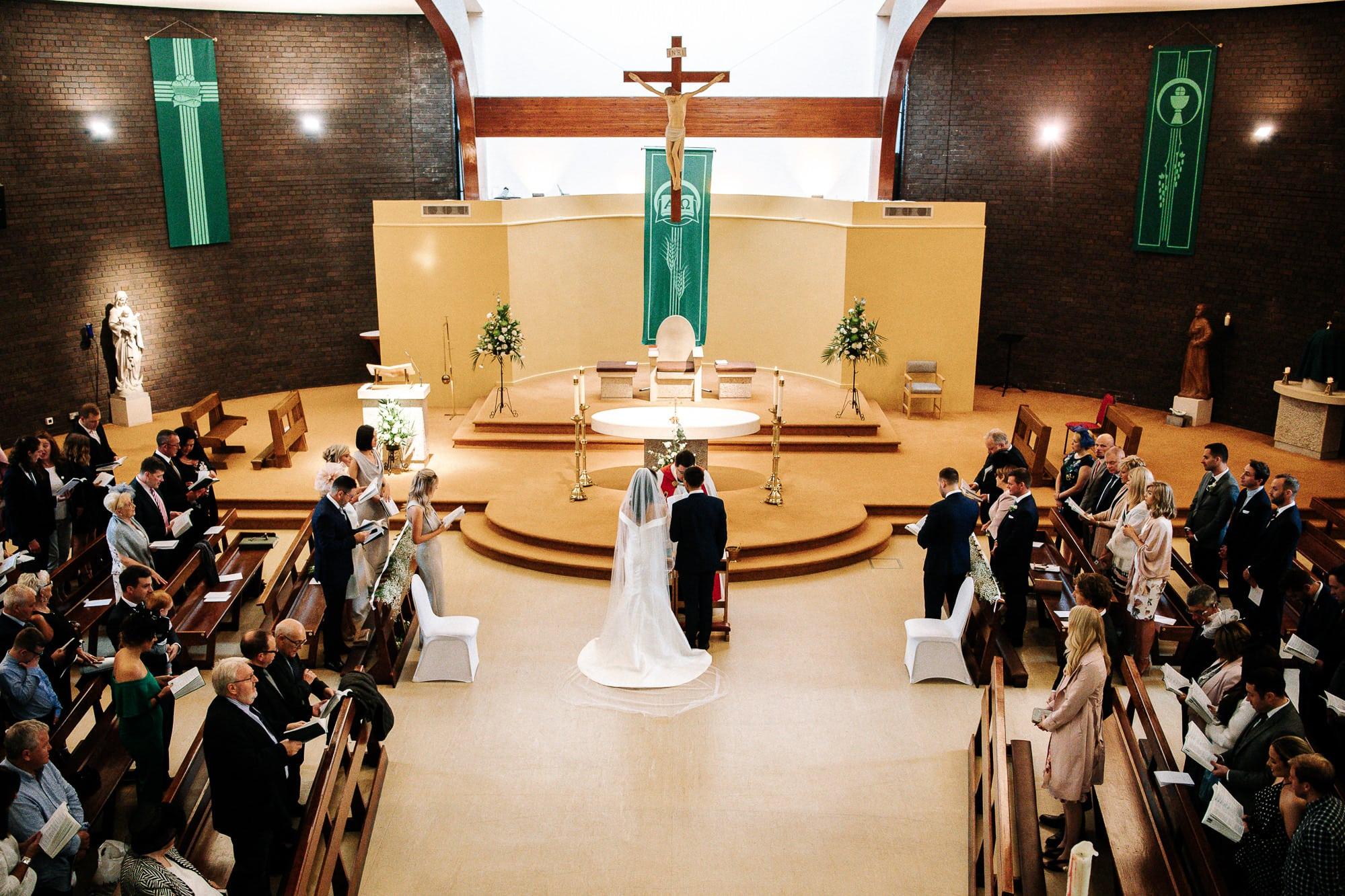 wide photo of the church with the bride and groom