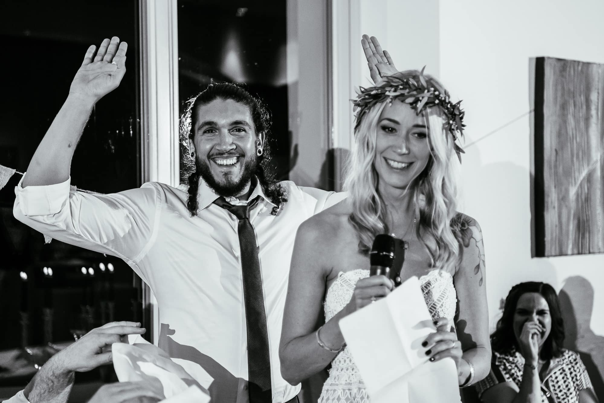 Bride and groom laughing with grooms arm in the air