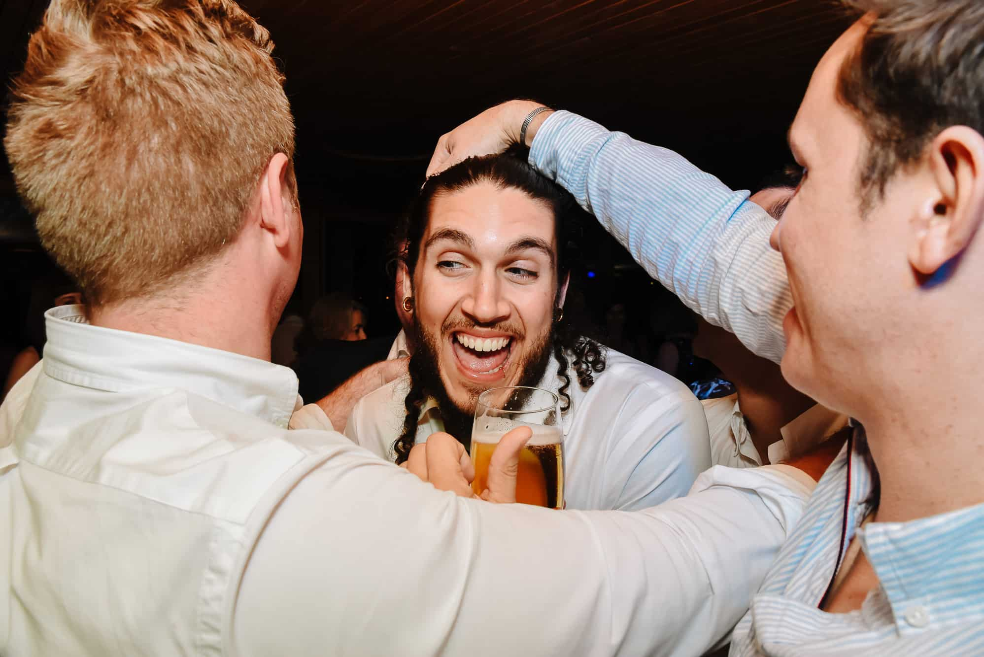 Groom being grabbed by friends and laughing