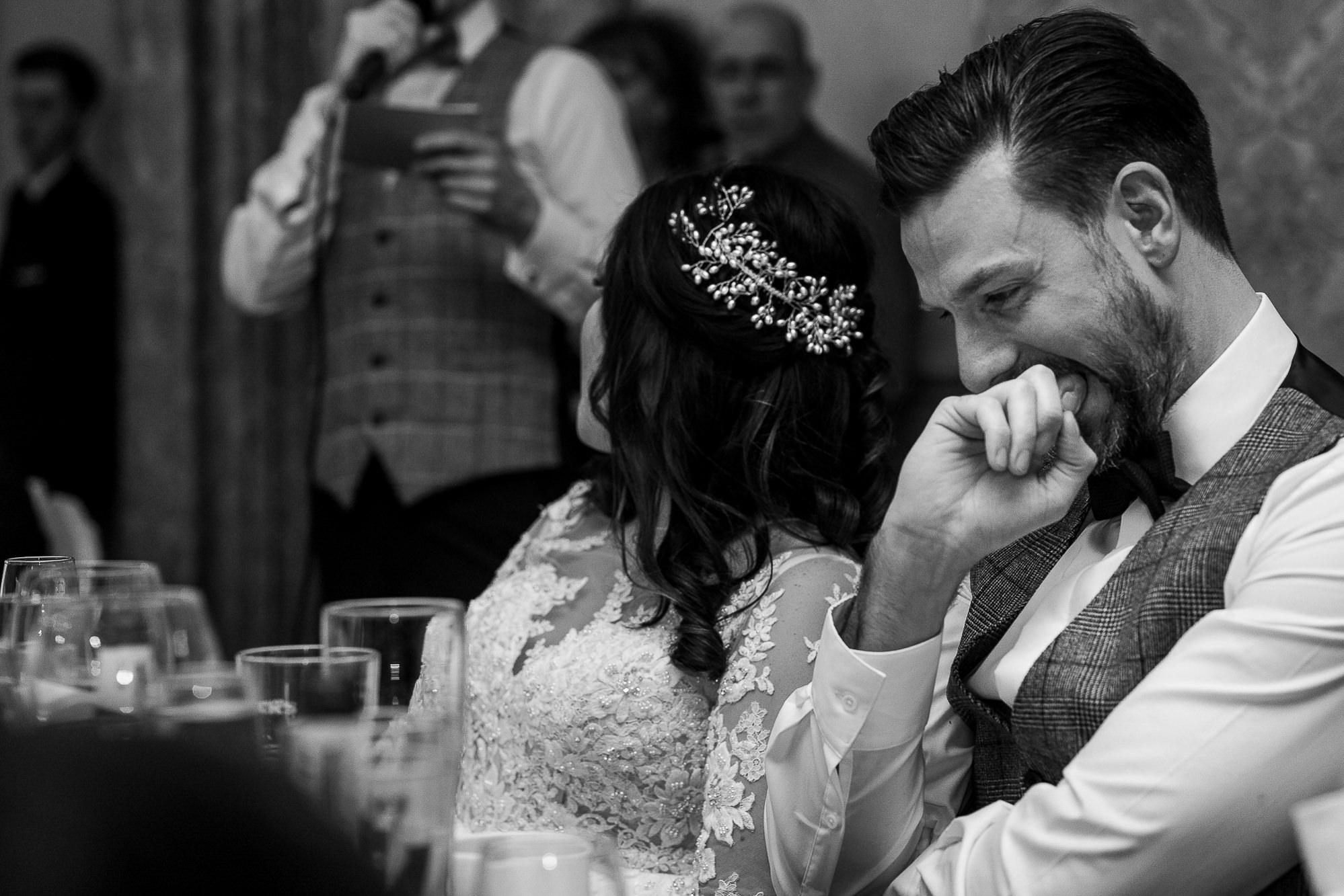 Groom with his hand in his mouth during best man speech