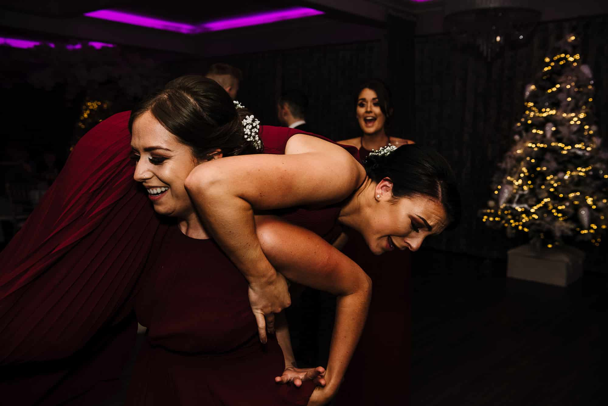Bridesmaids dancing carrying one another
