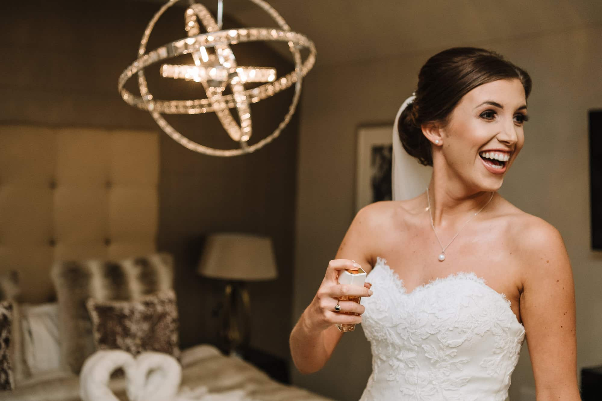 Bride laughing and spraying perfume