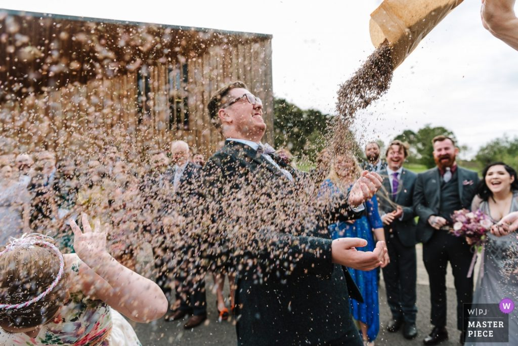 Bride and groom being covered in confetti