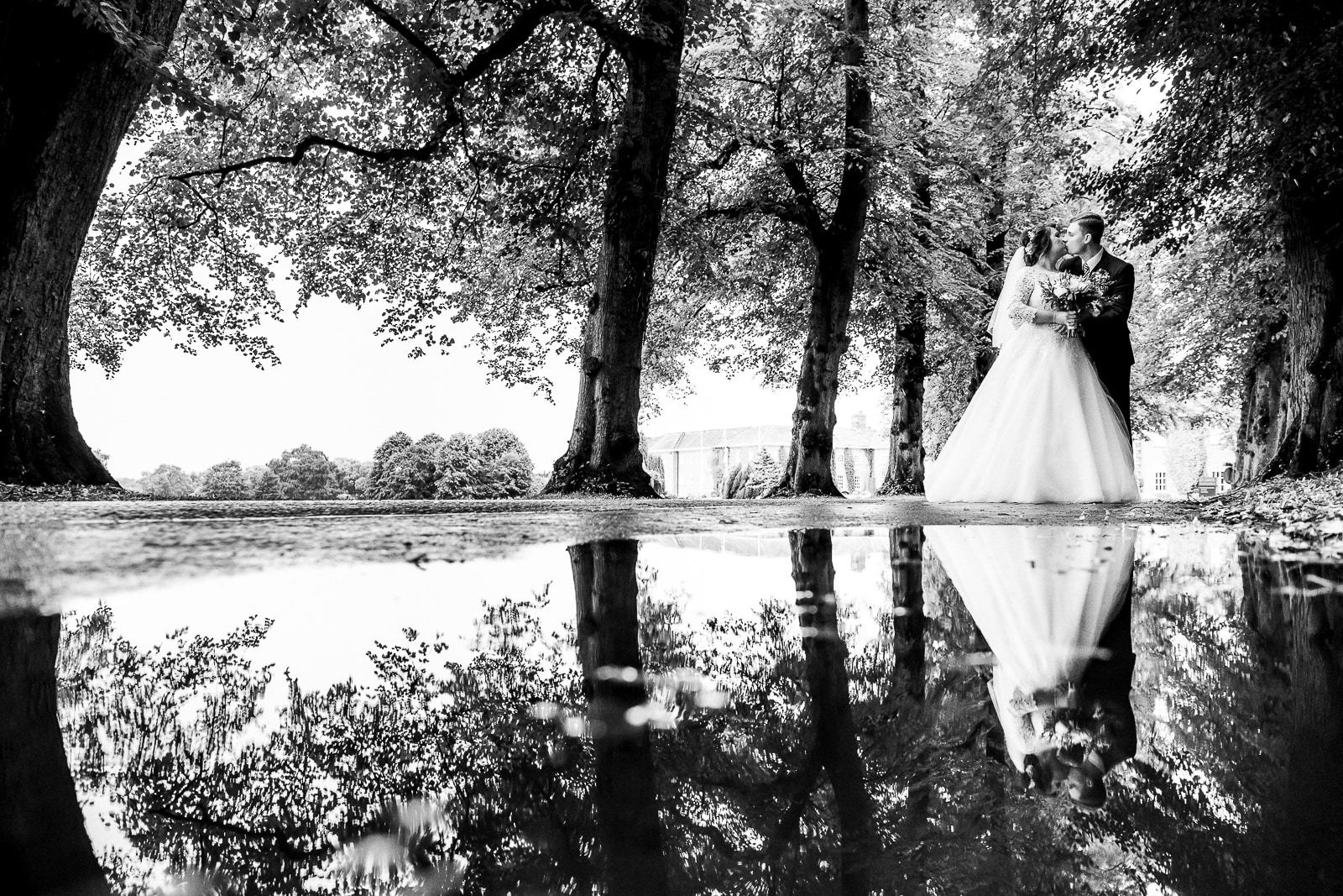 bride and groom hugging with reflection in a puddle