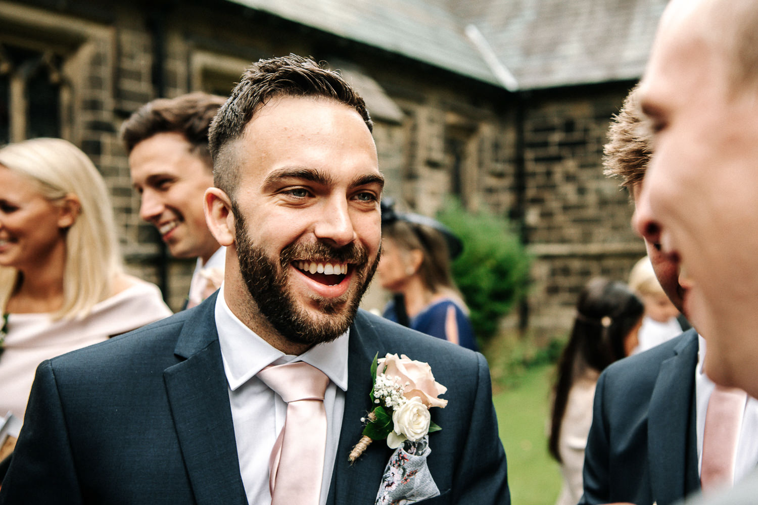 Bestman laughing with guests outside the church