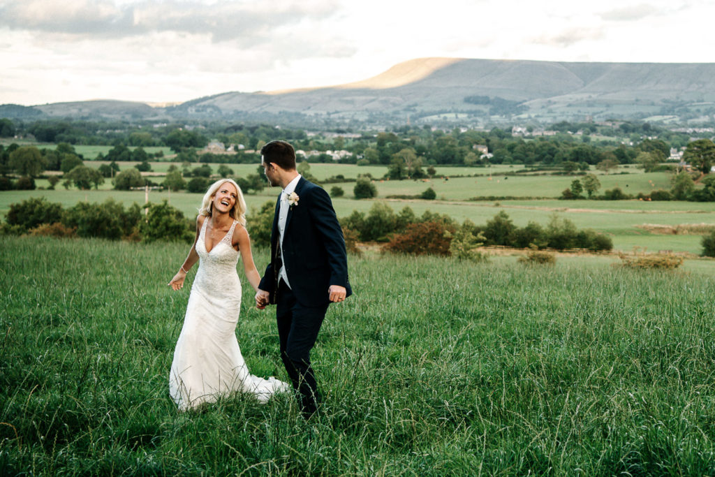 Bride and groom smiling in the field