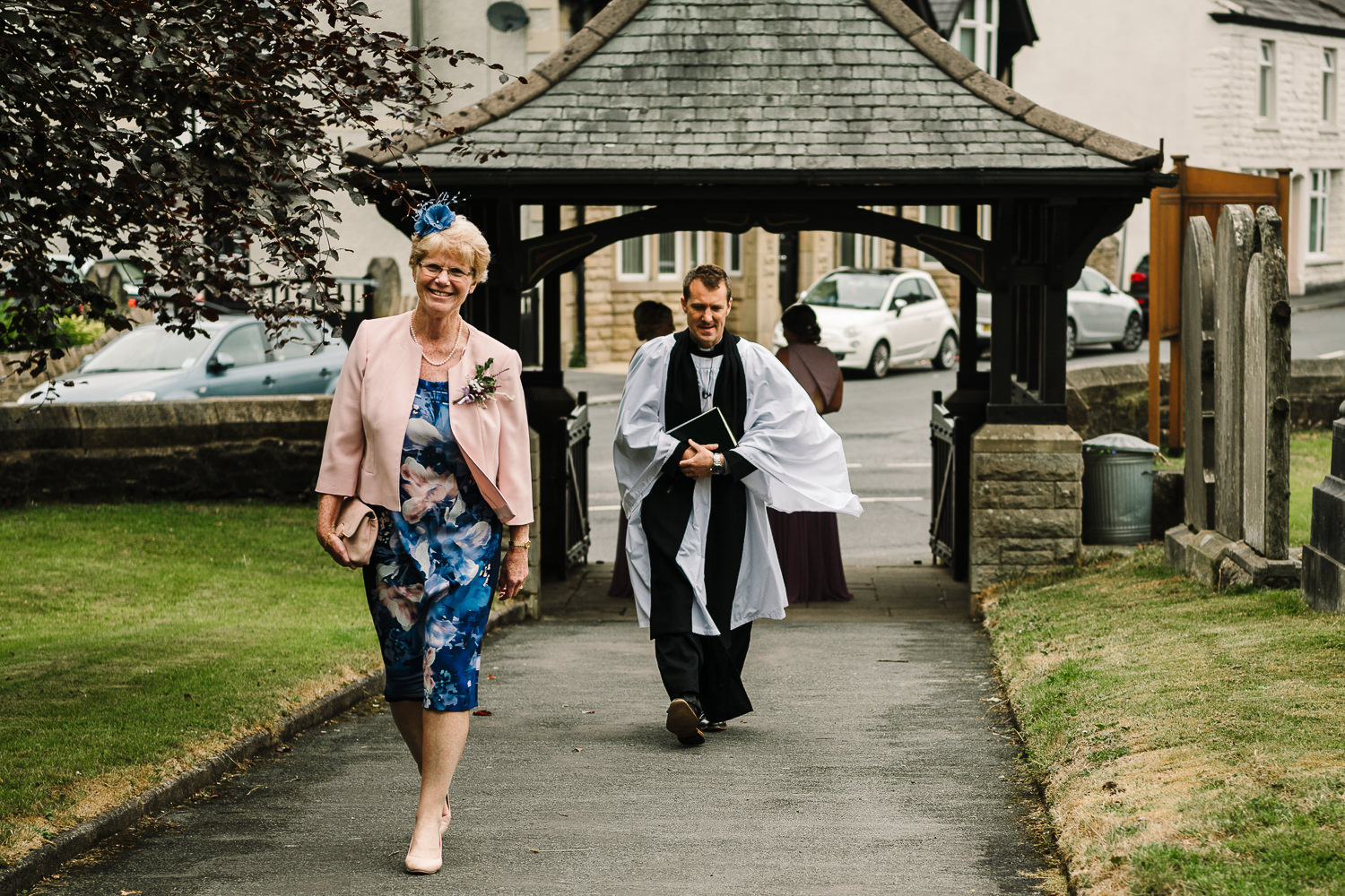 Mother of the bride and the vicar walking up to church