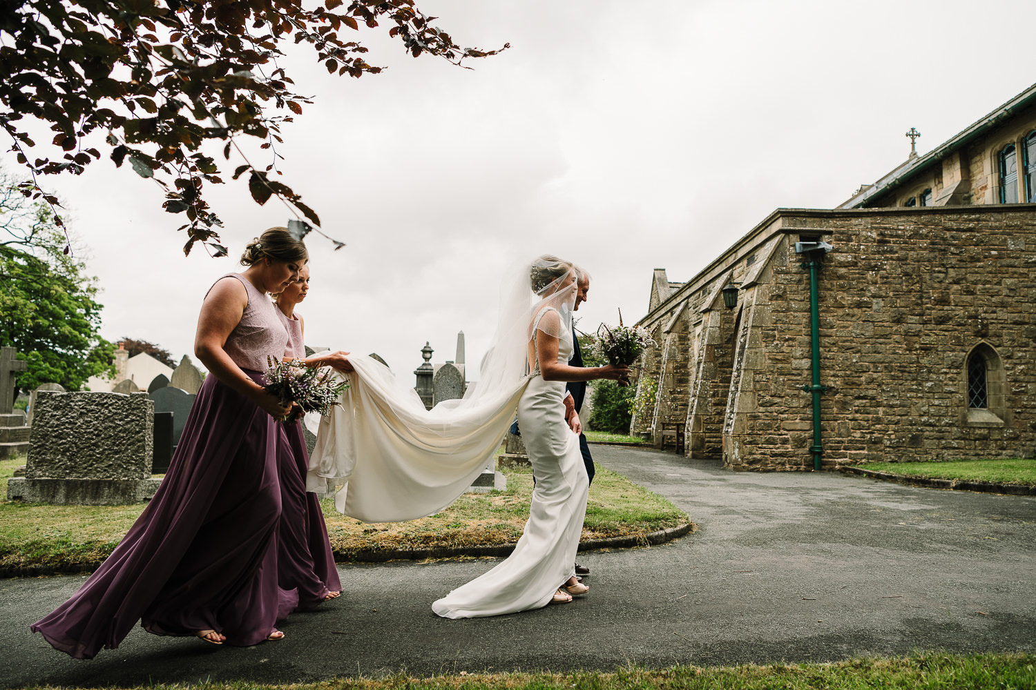 Bride walking to church with her bridesmaids carrying her dress