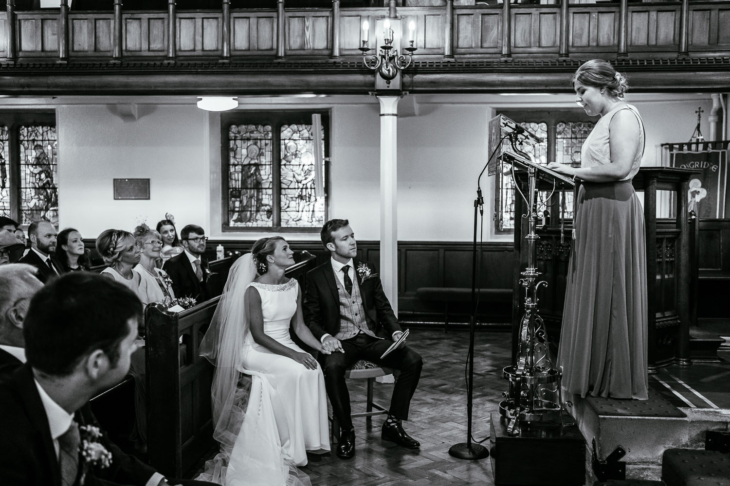 Bride and groom listening to a reading by a bridesmaid