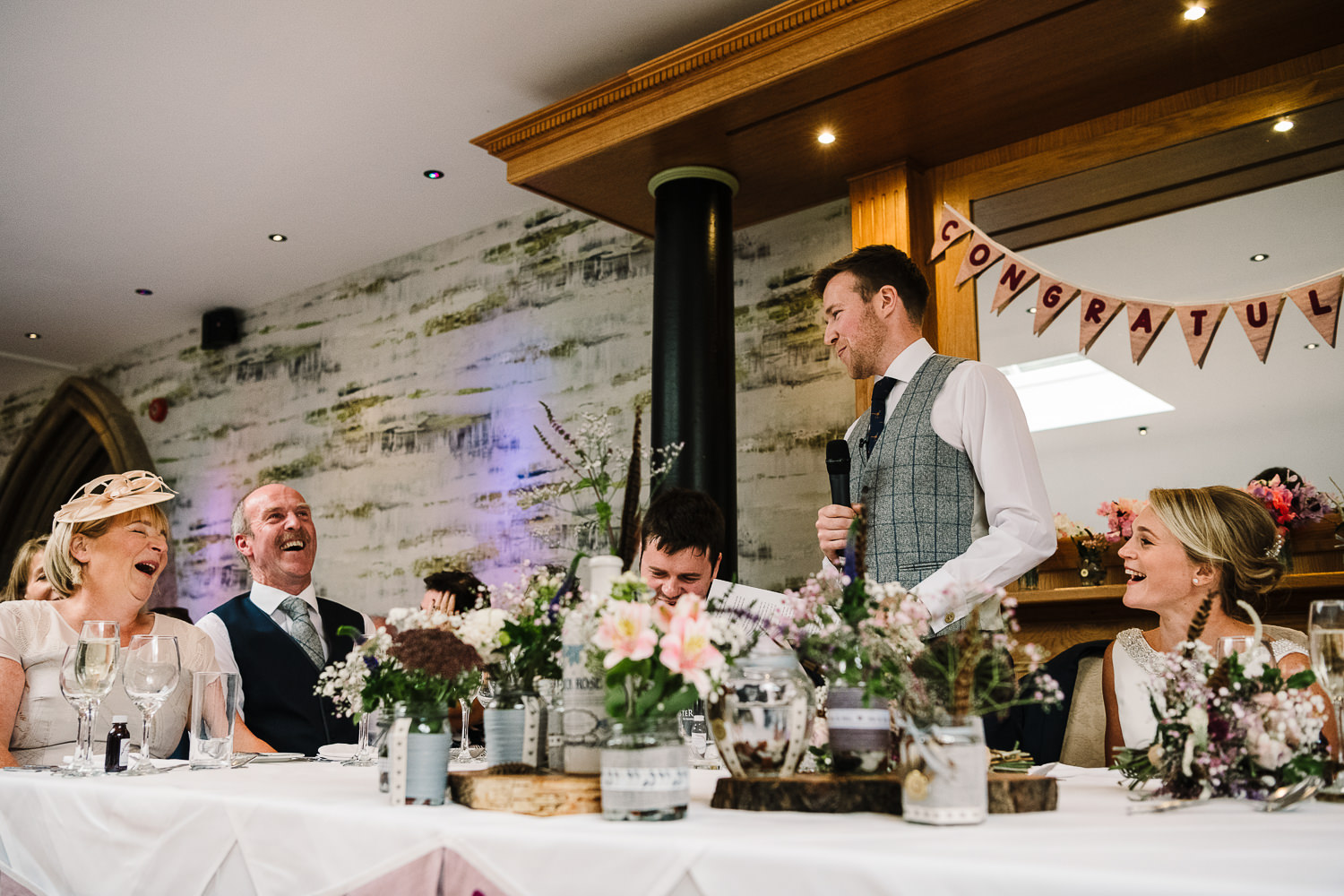 Groom speech and guests laughing on top table