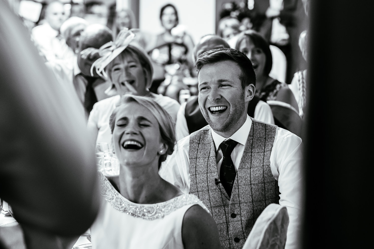 Bride and groom laughing during best man speech