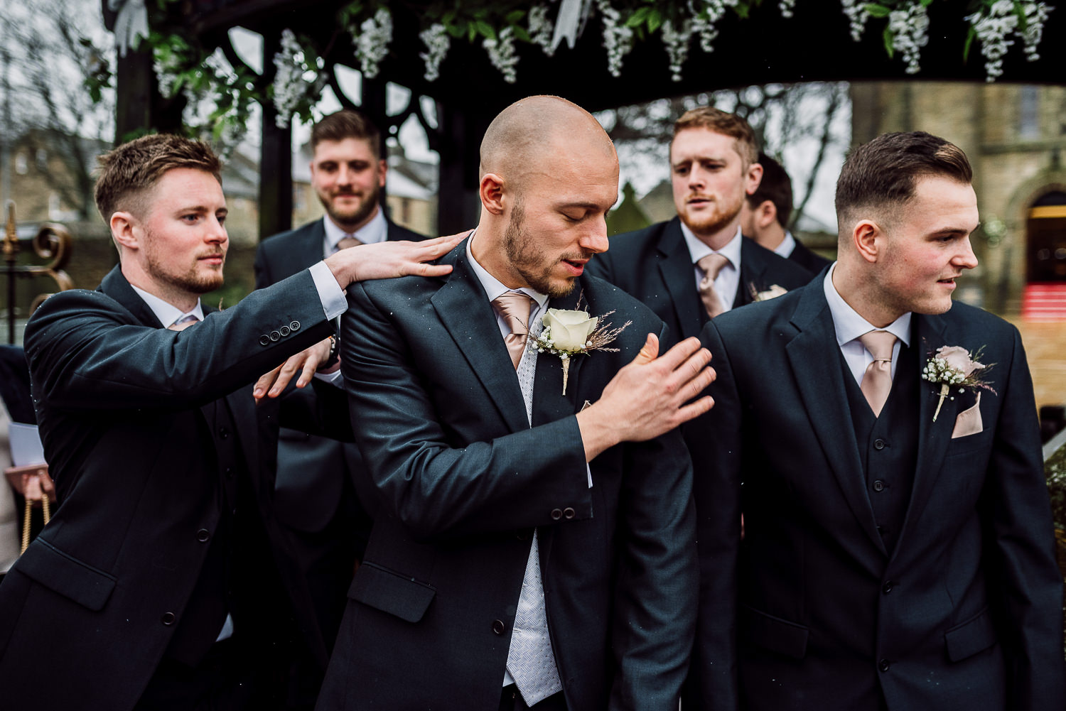 Groom getting confetti off himself