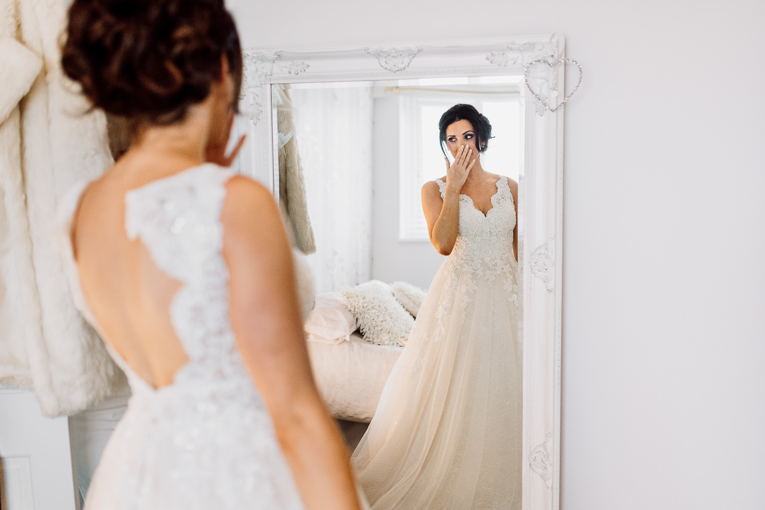 Bride putting on her wedding dress and looking in the mirror