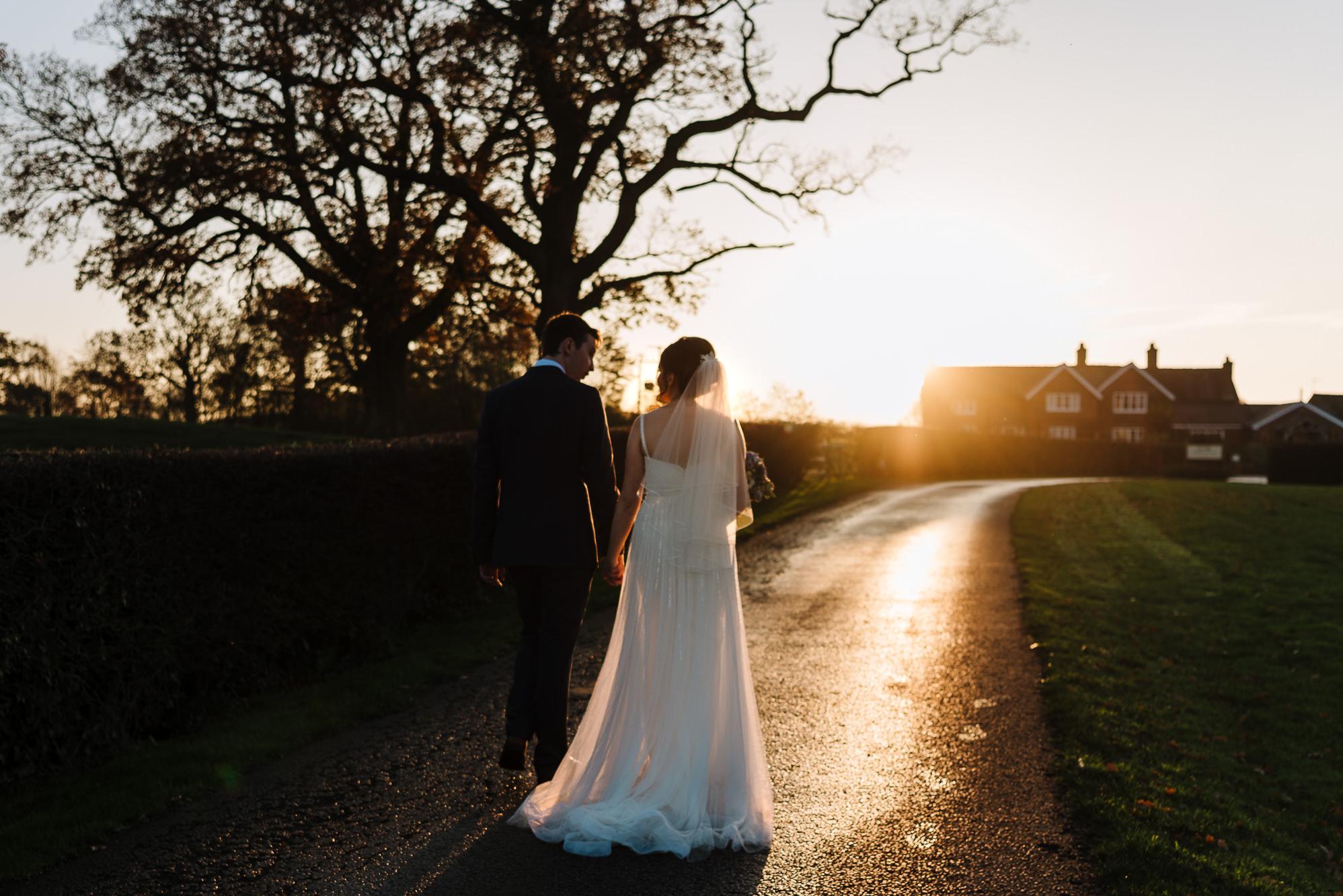 Couple walking in sunset towards Sandhole Oak Barn