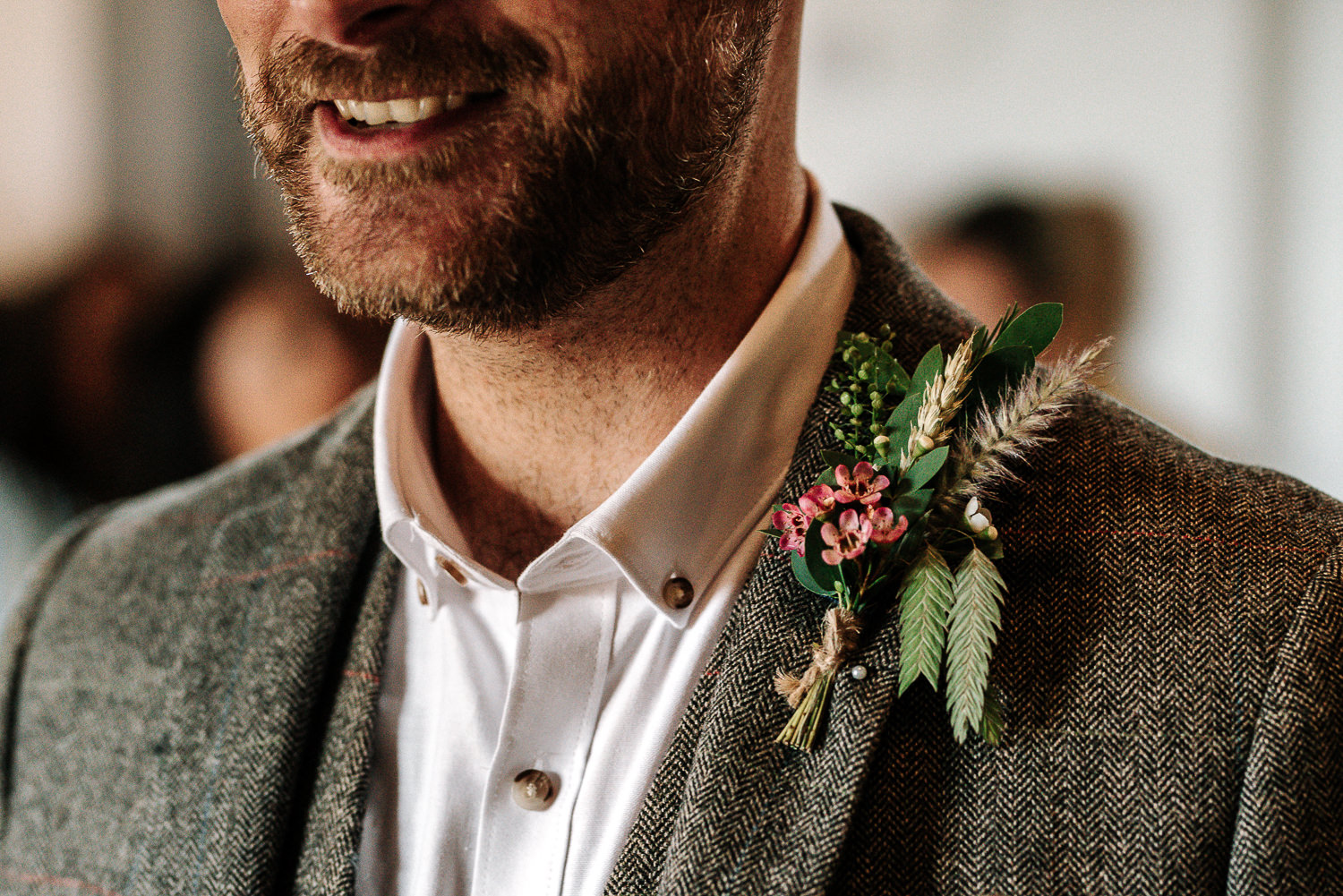 Groom smiling with flower on show