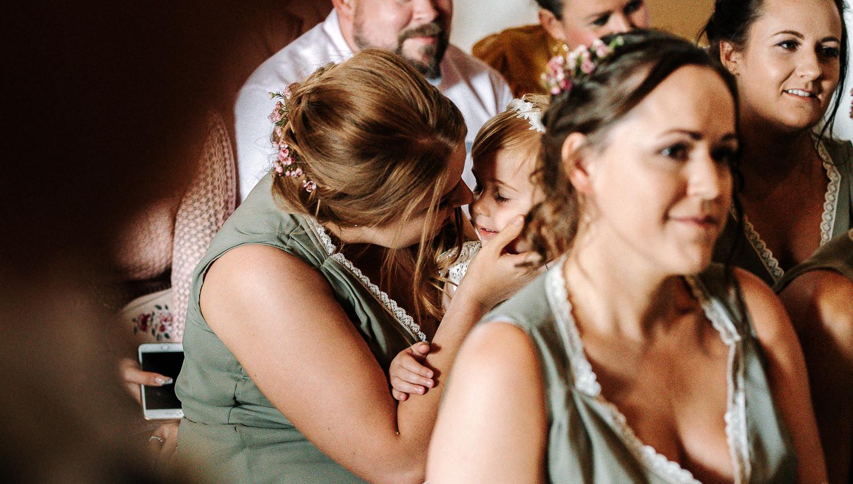 Bridesmaid kissing flower girl
