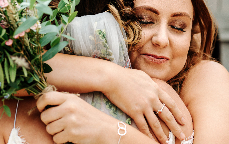 Bridesmaid hugging her sister the bride