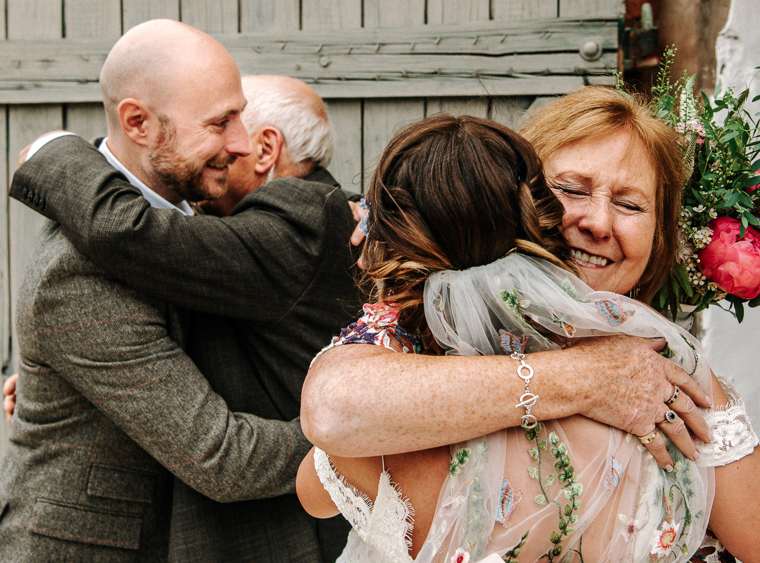 bride and groom hugging parents
