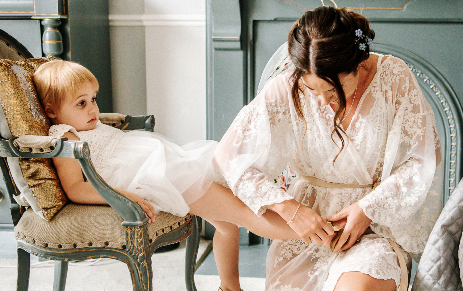 bride putting the shoe on of her flower girl