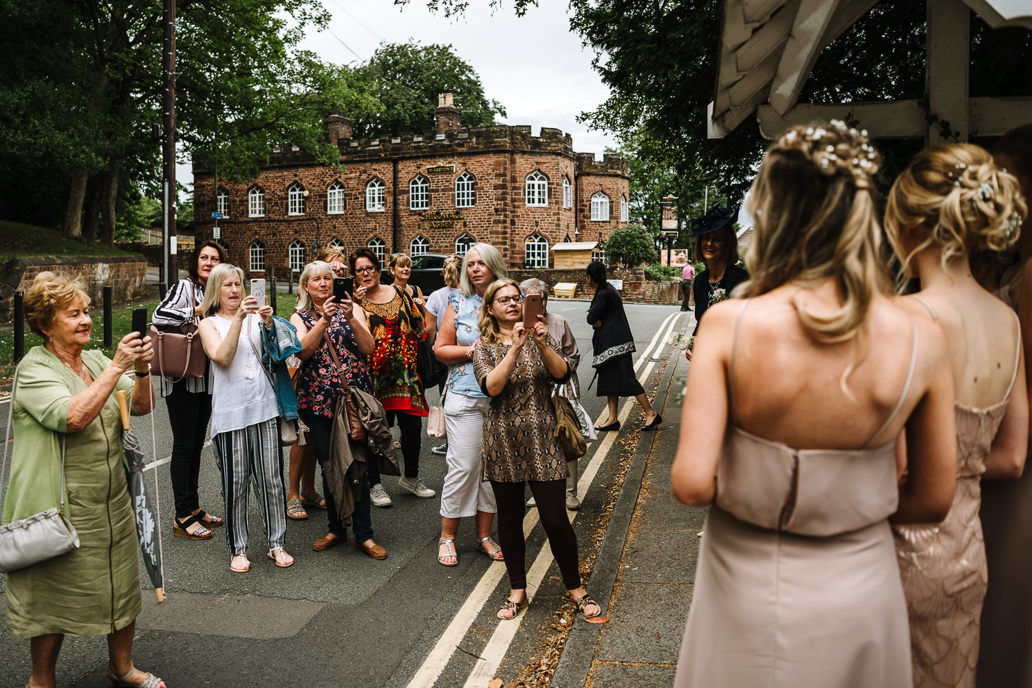Bridesmaids being photographed by loads of women outside the church