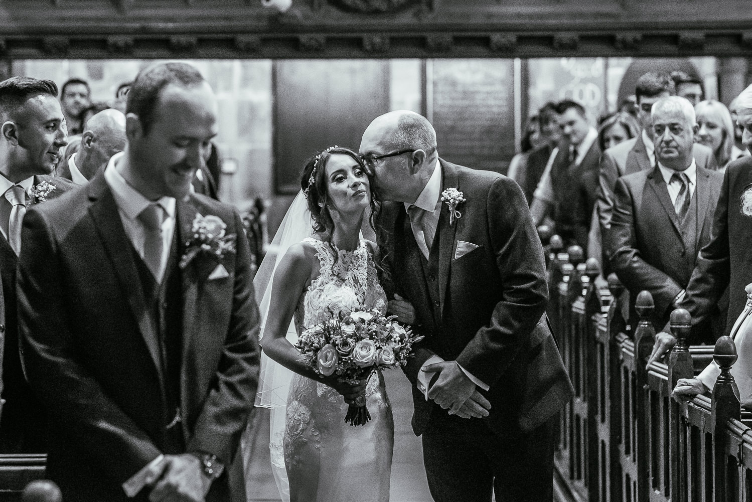 Bride walking down the aisle with her dad being kissed