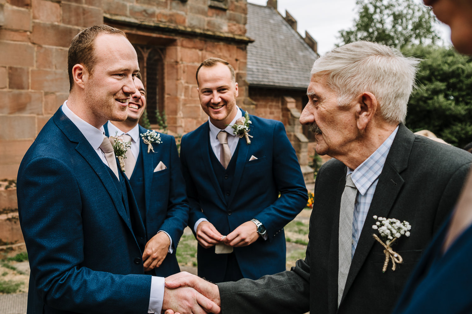 Groom shaking hands with grandad outside the church