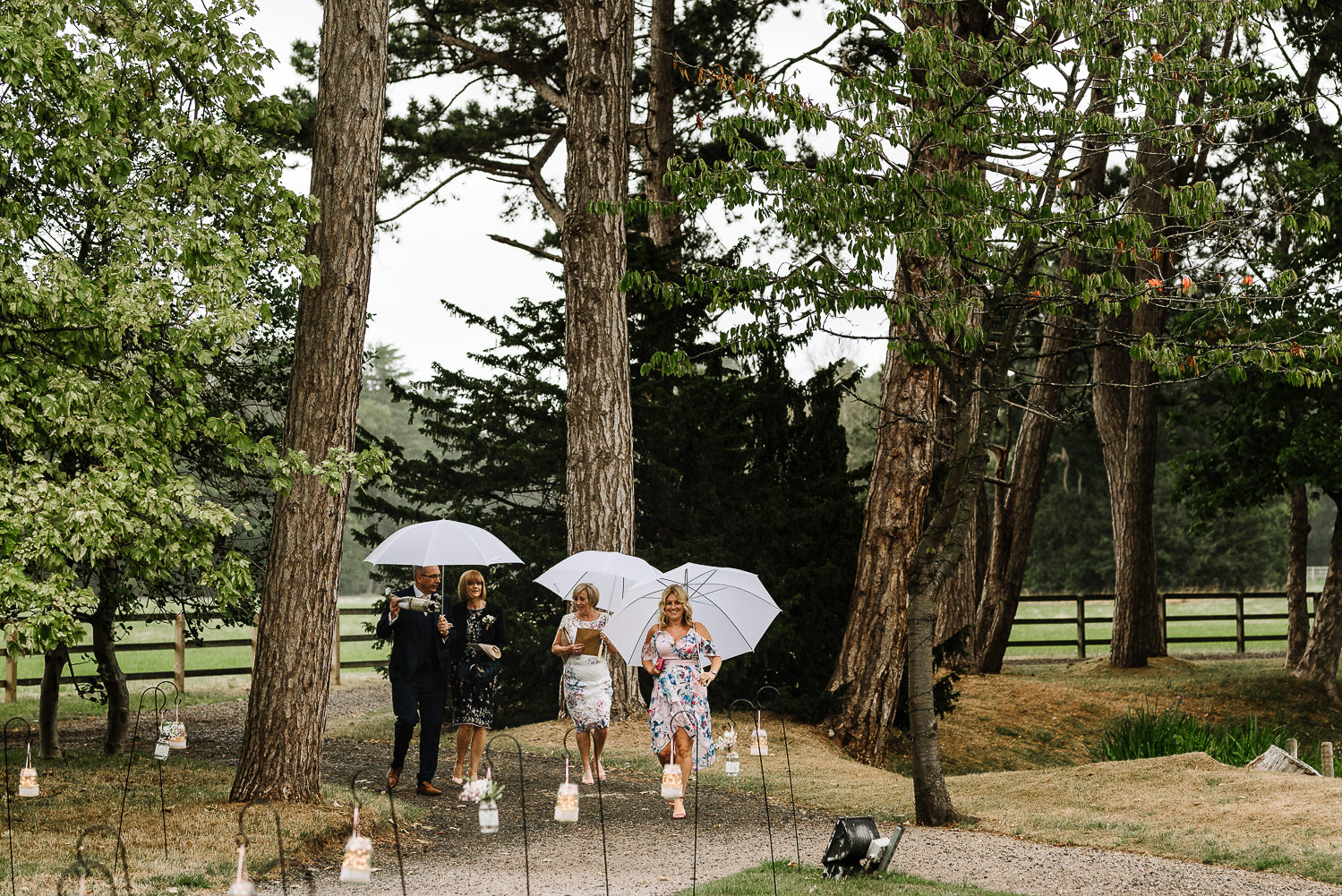 Guests walking to the pavilion with umbrellas
