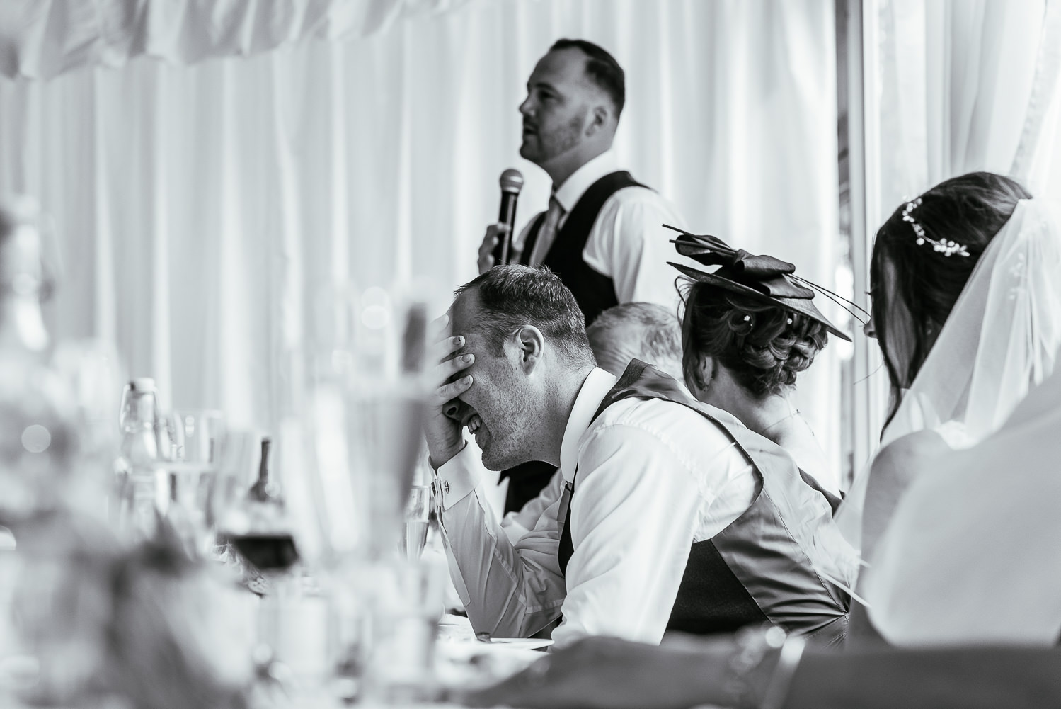 Groom with his head in his hands during speeches