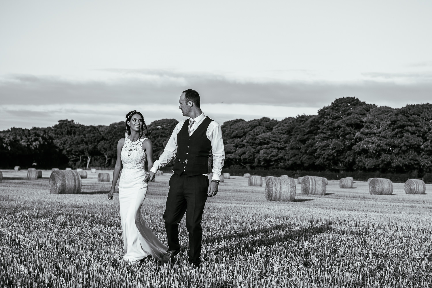 Bride and groom walking in fields with hay bales