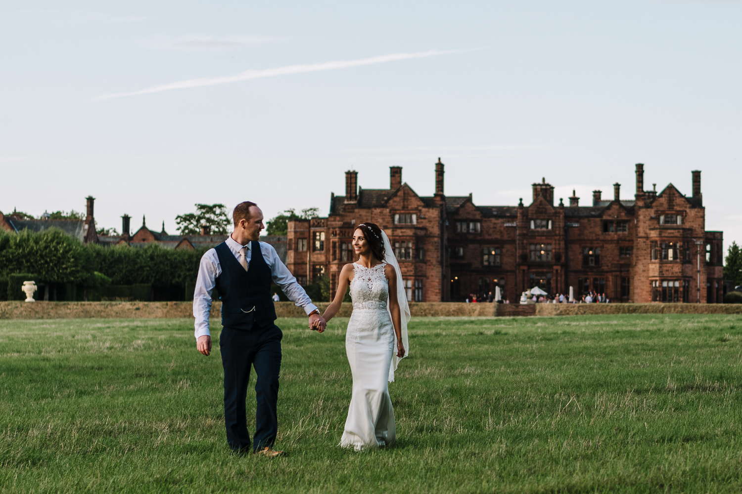 Bride and groom walking with Thornton Manor in the background