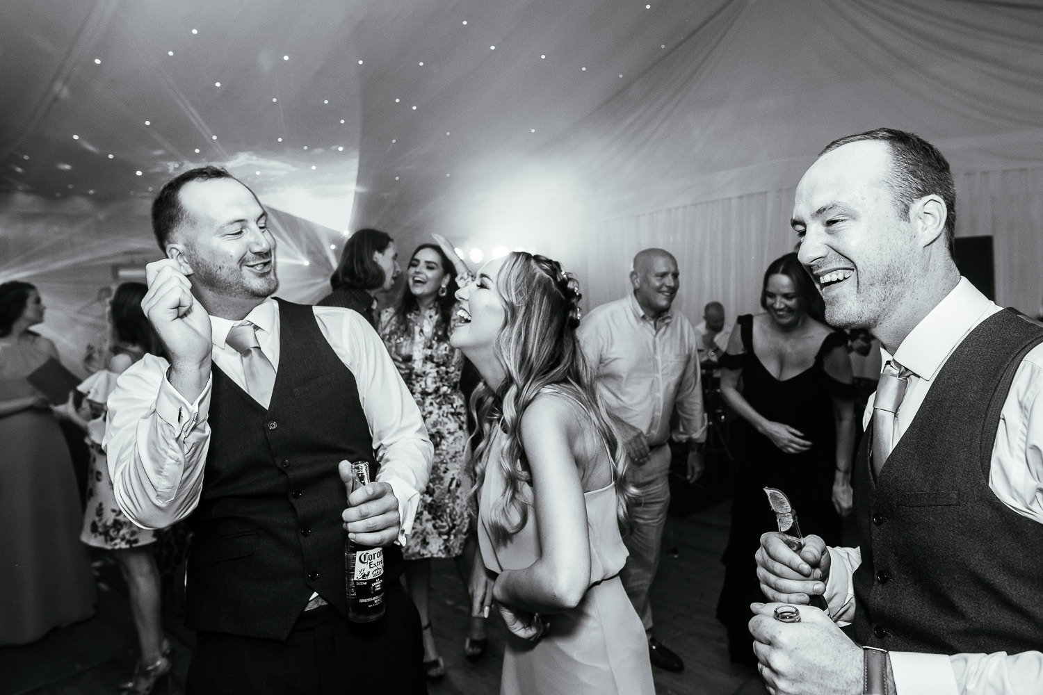 Groom, best man and bridesmaid dancing