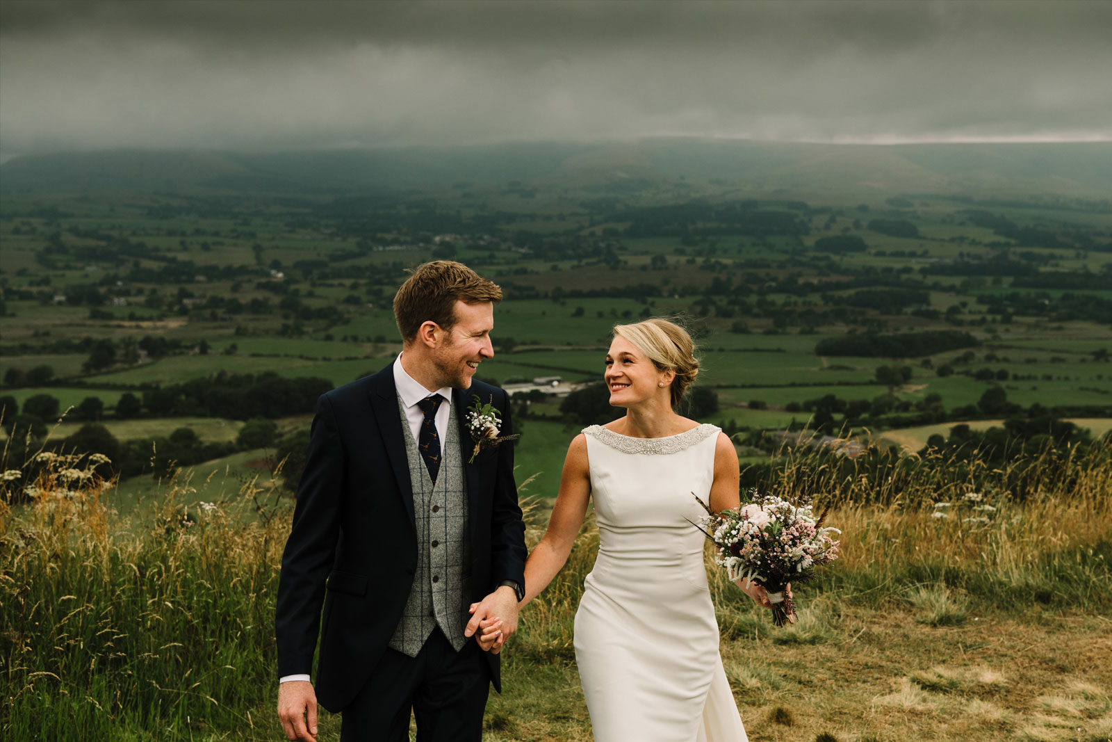 Bride and groom walking and smiling in the Ribble Valley countryside