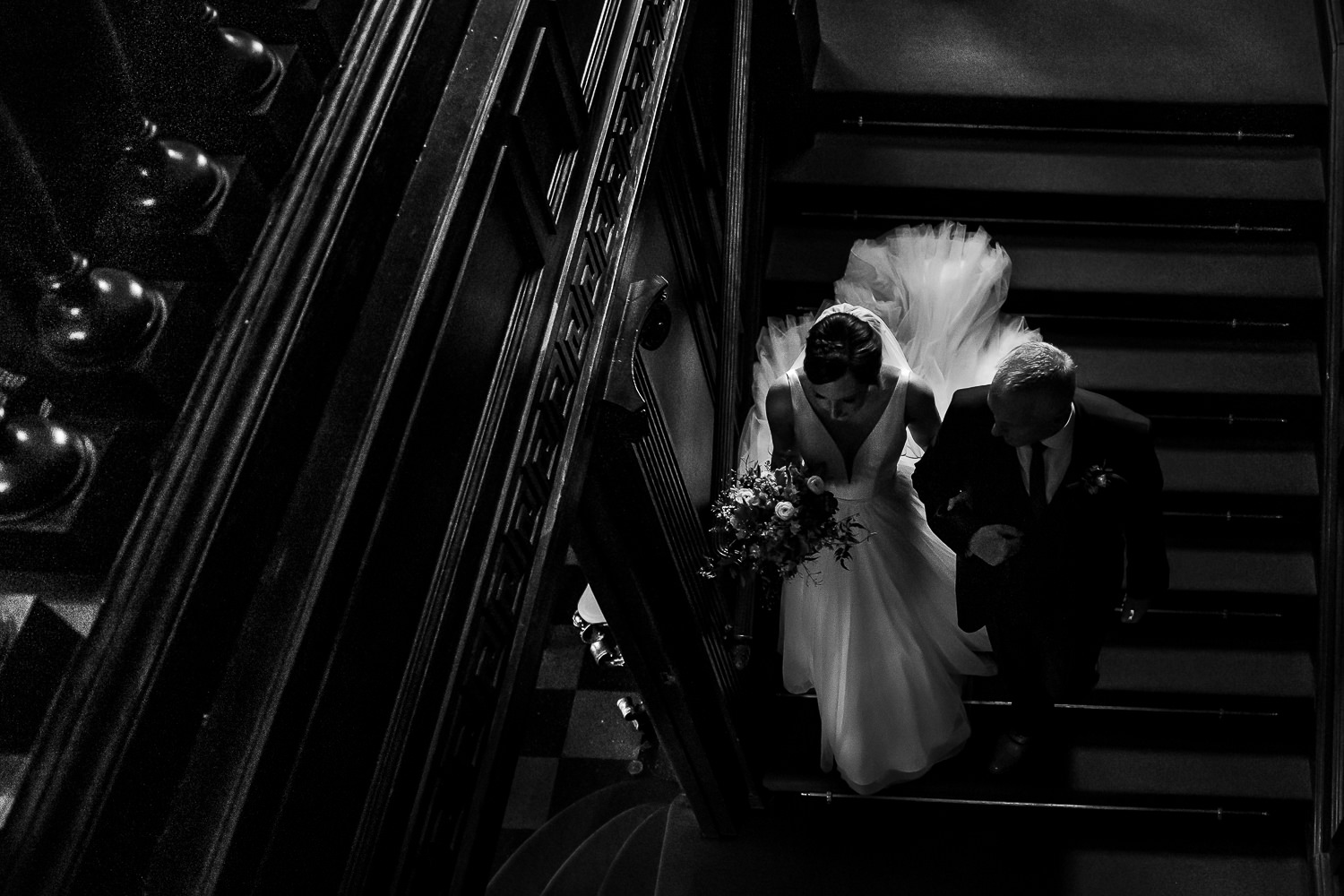 Bride and her dad walking down the stairs