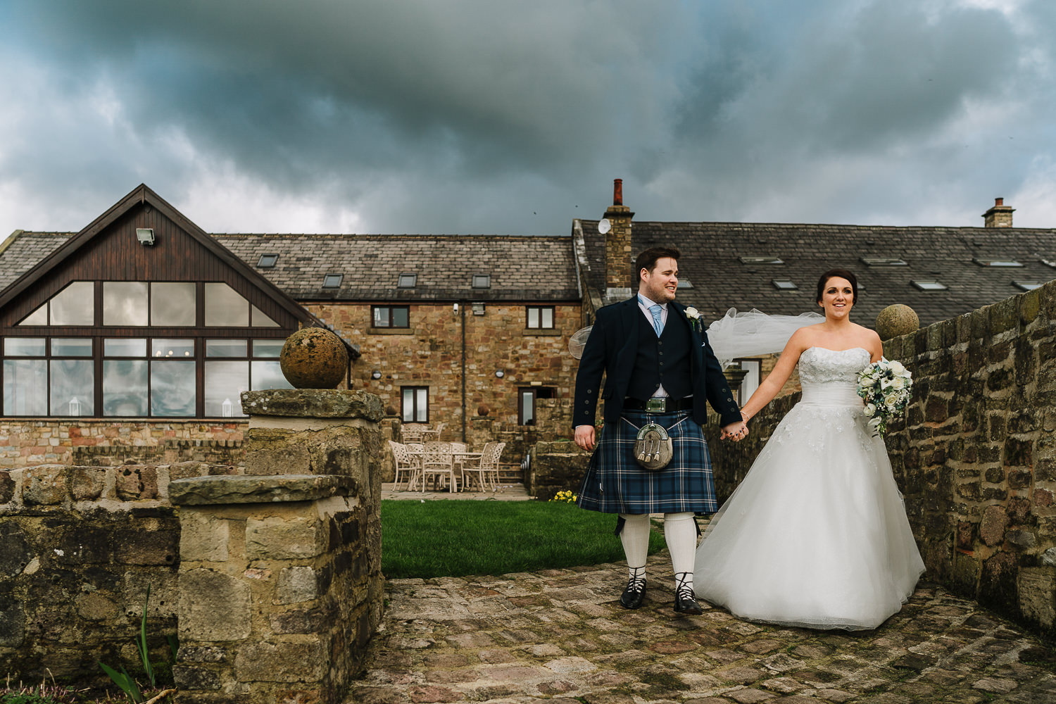 bride and groom walking outside Beeston manor