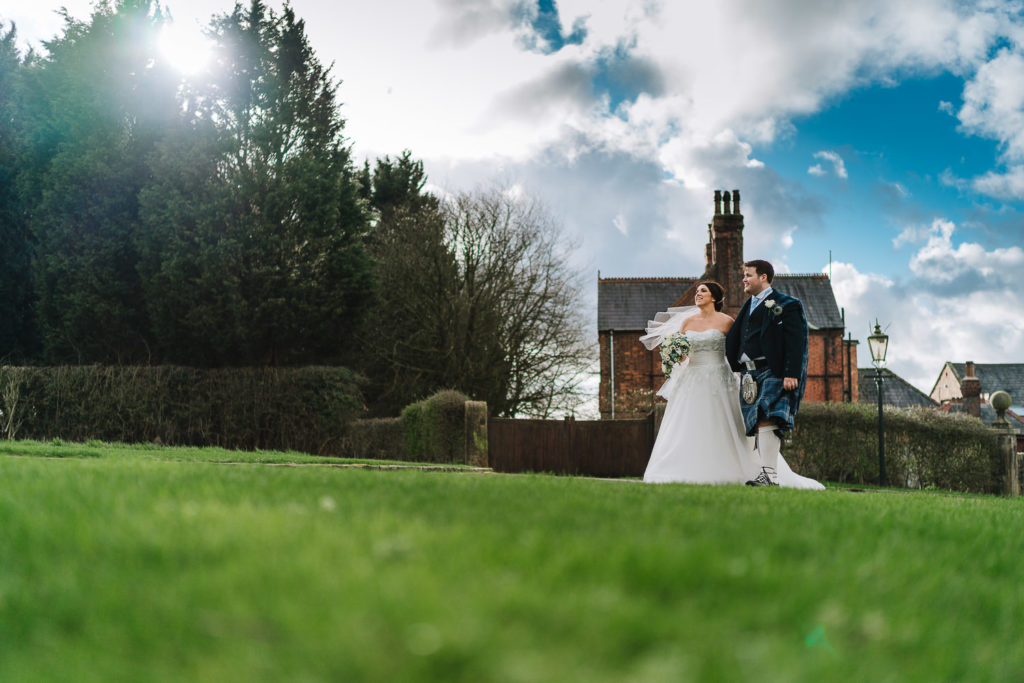 bride and groom walking outside bestow manor with the sun coming through