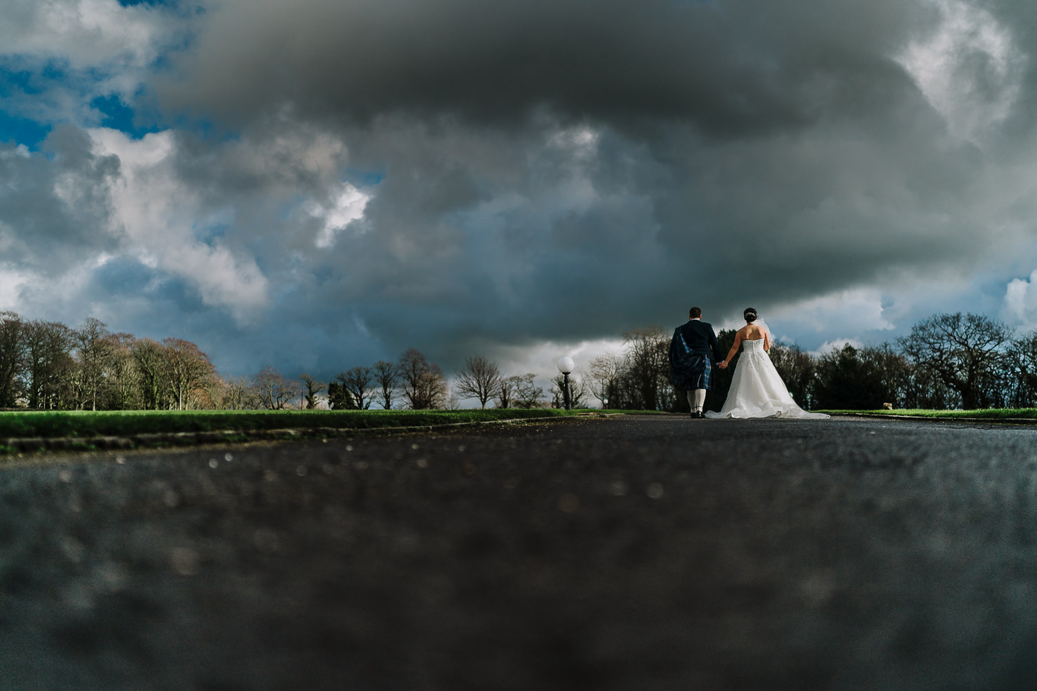 bride and groom walking in the sun with dark clouds