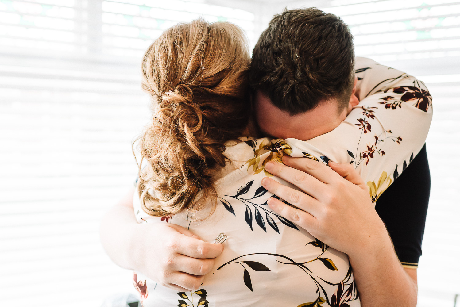 Groom crying into his mums arms after getting a gift from bride
