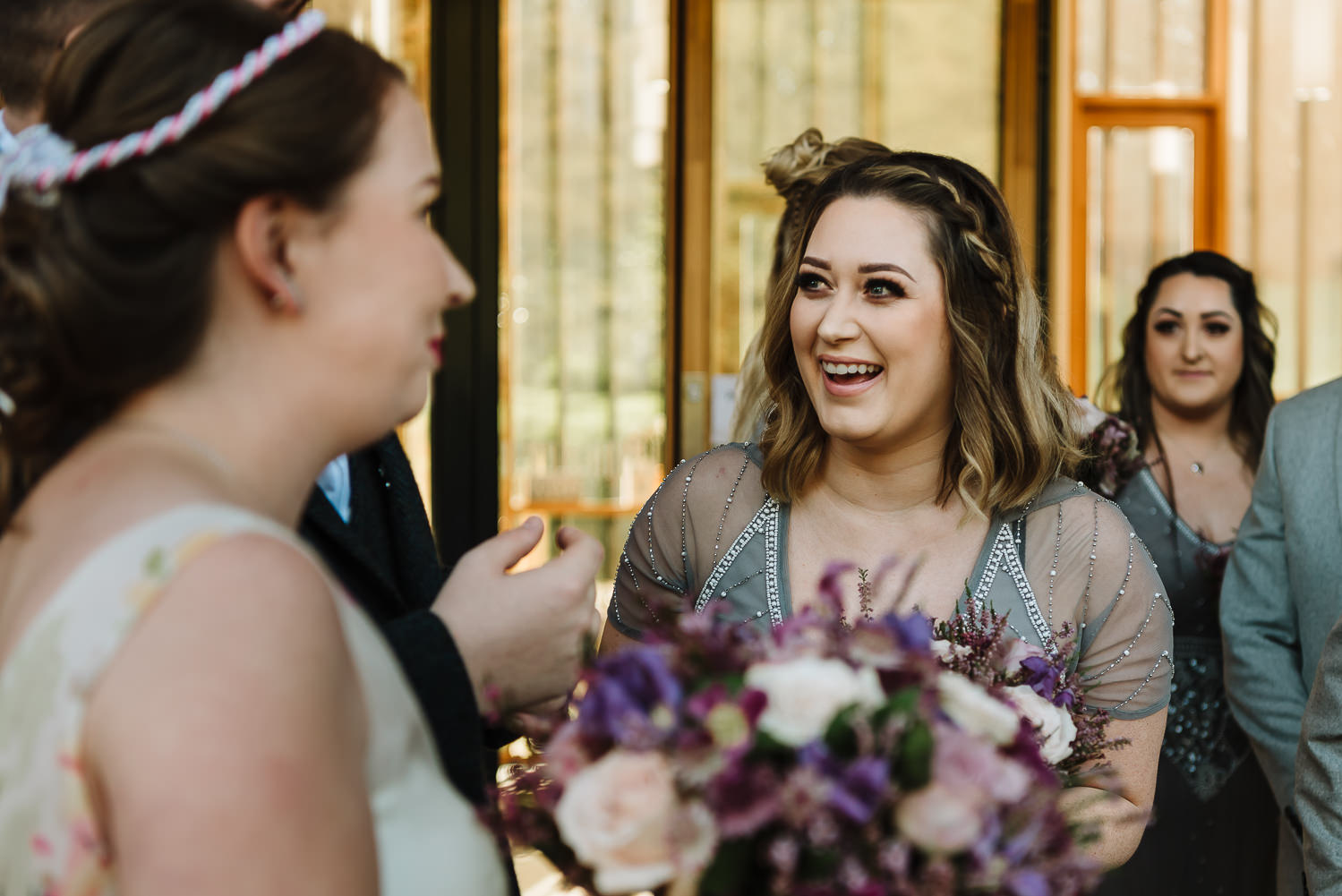 bridesmaid laughing with he couple