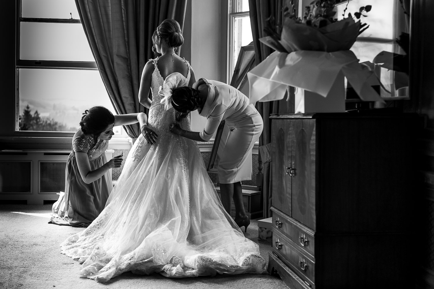 Bride having her dress put on by bridesmaid and mother of bride