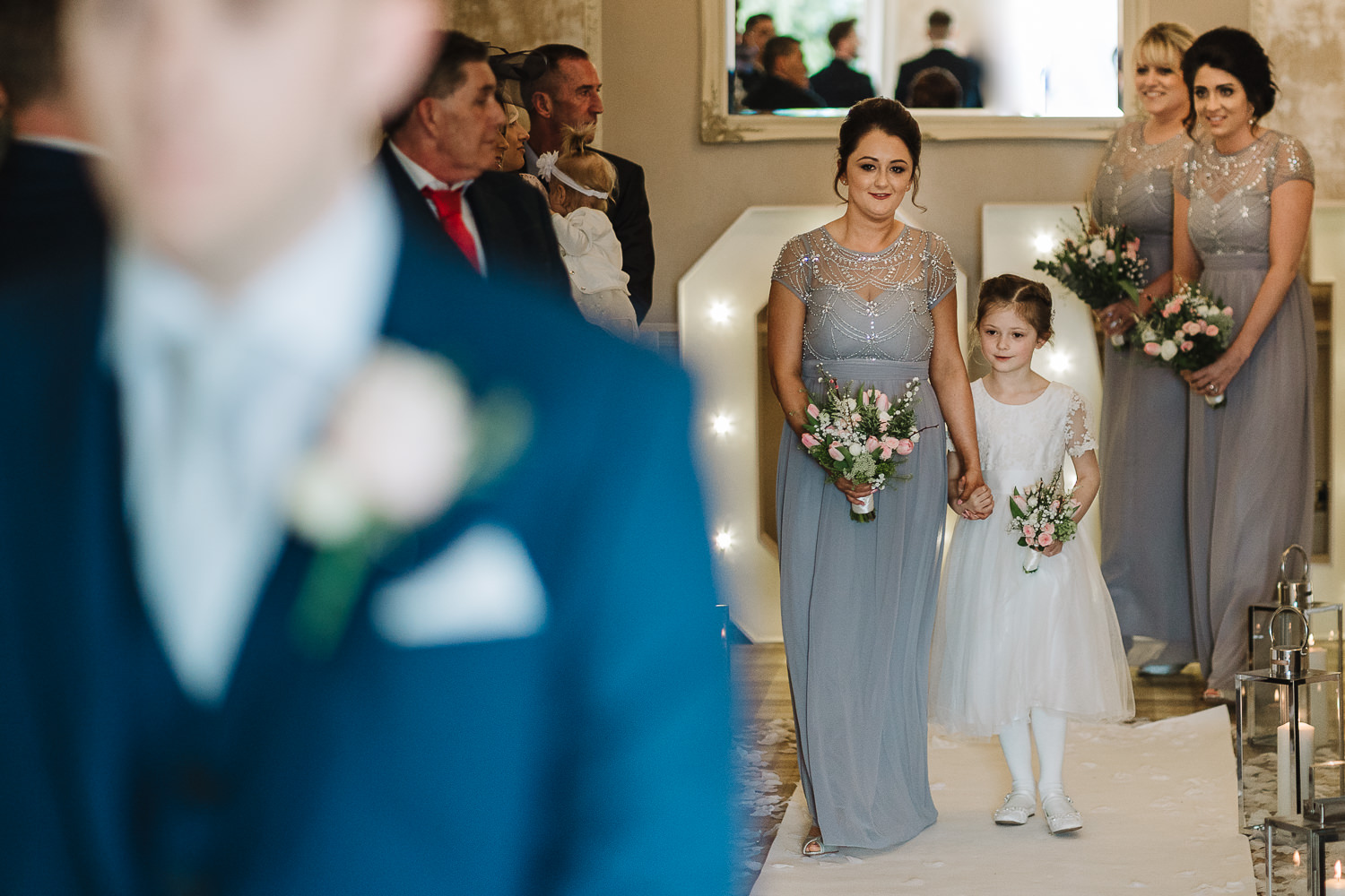 Flower girl and bridesmaid walking down the aisle