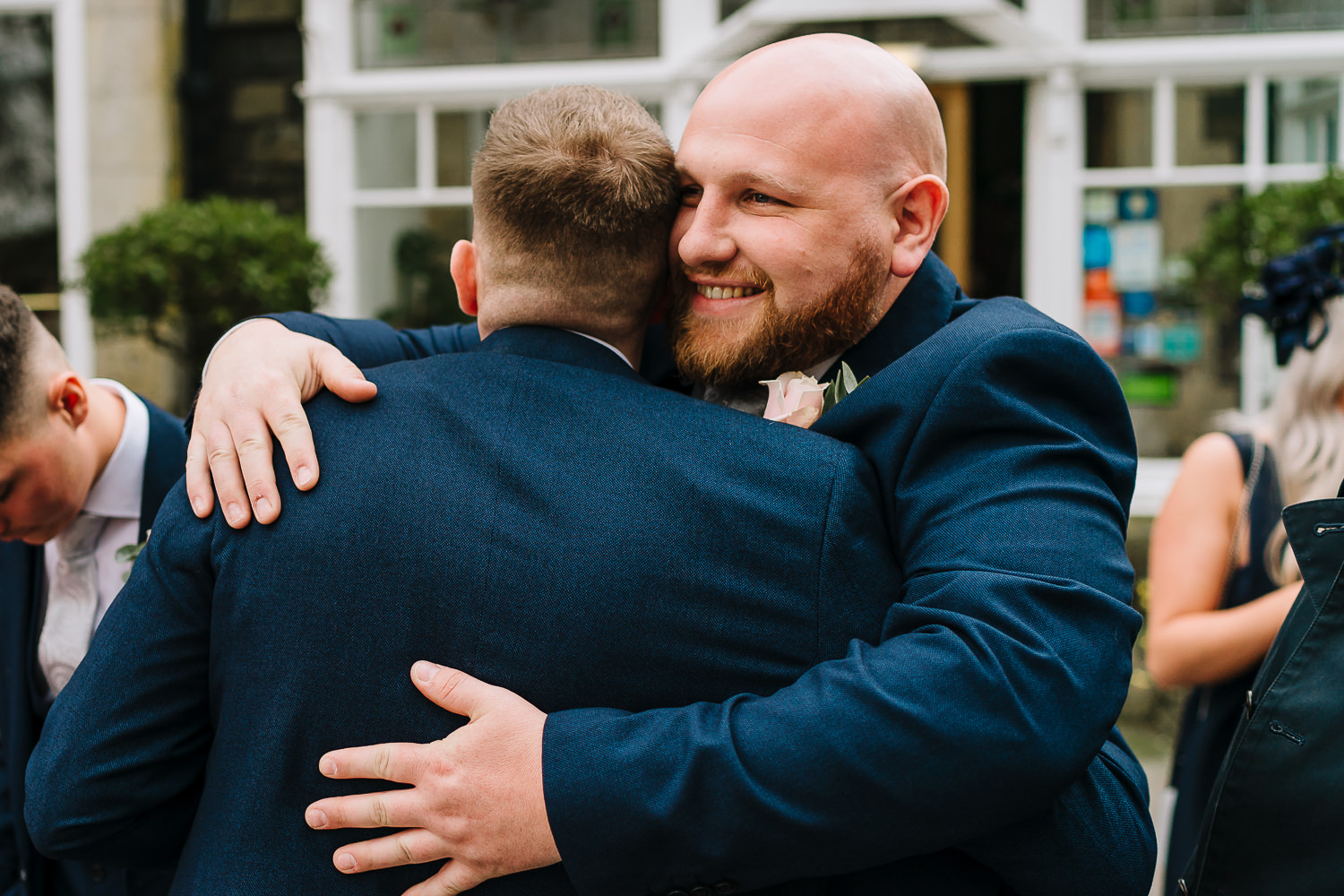 Groom being hugged by an usher
