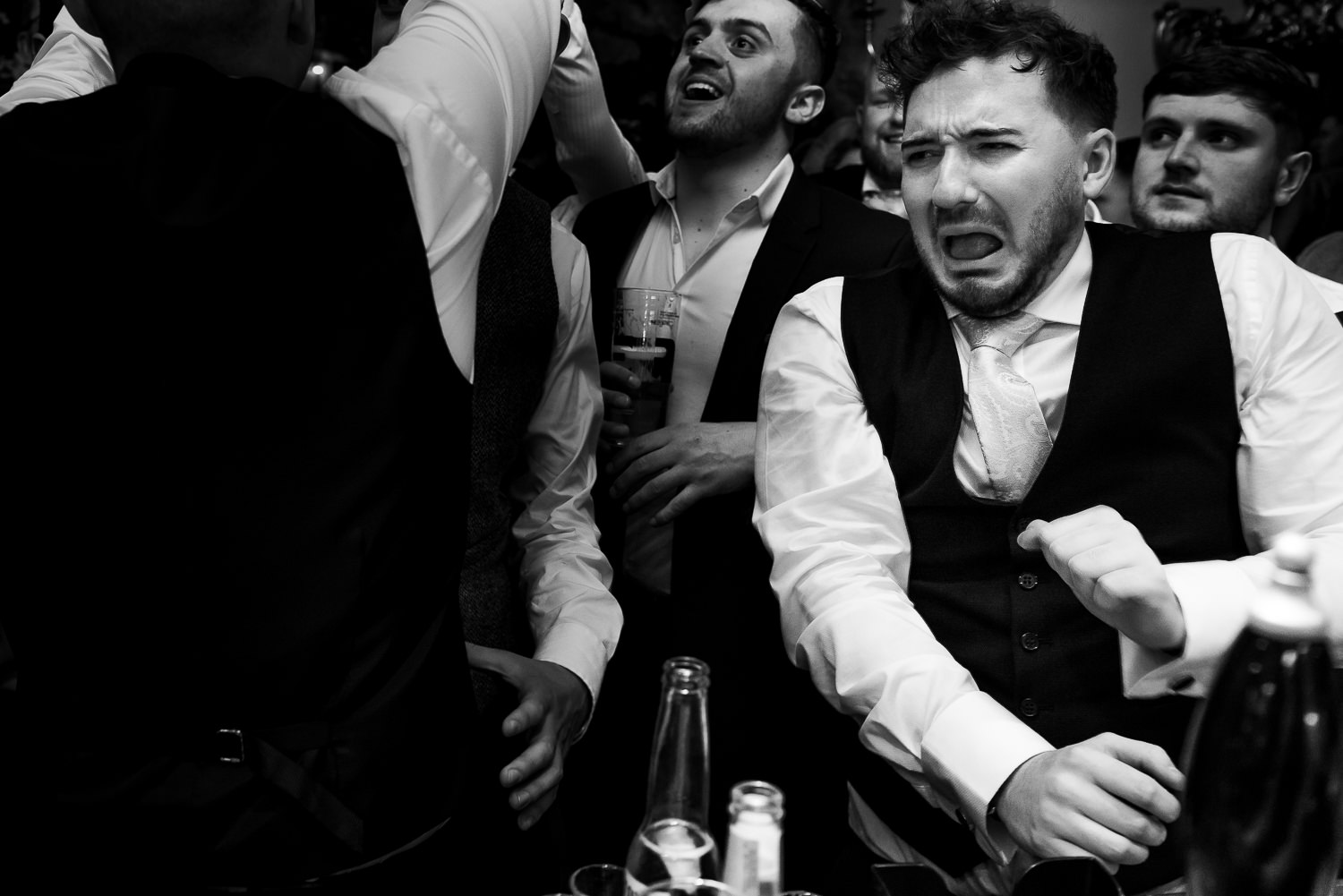 Best man pulling a face after a shot.