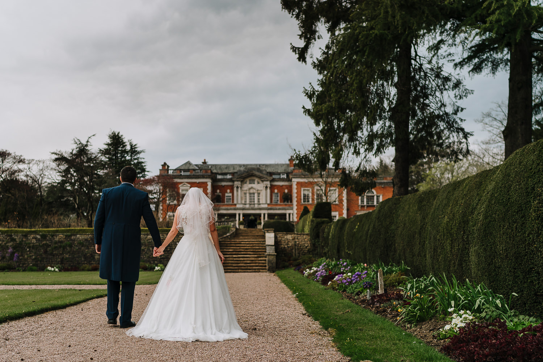 Bride and groom walking towards Eaves Hall