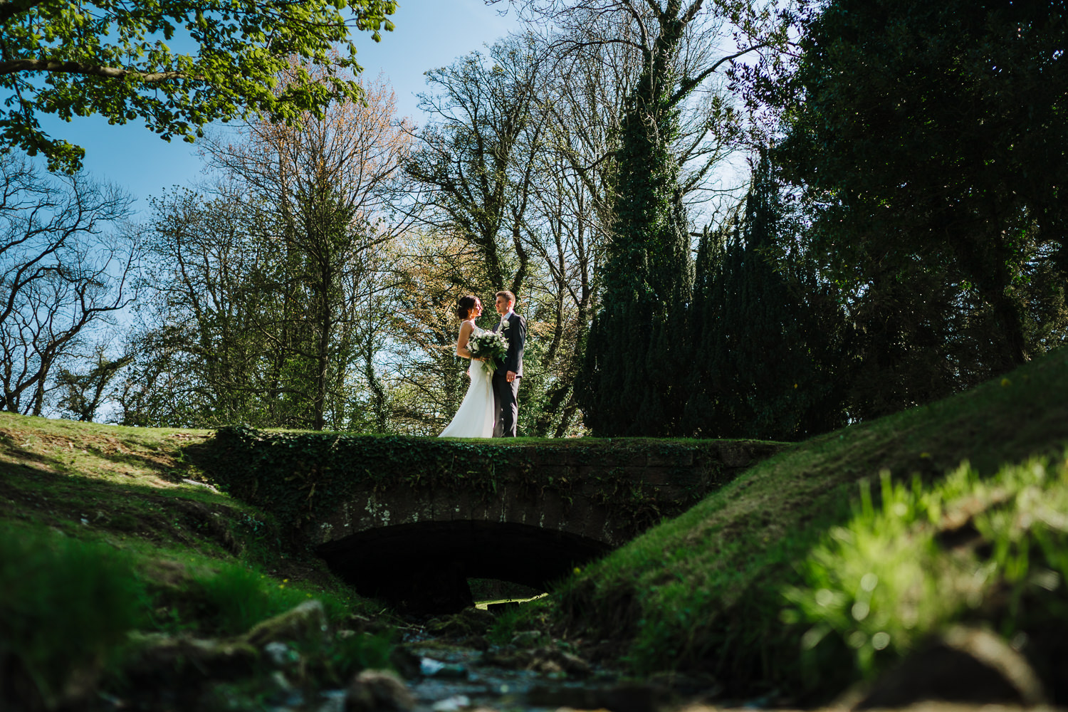 Bride and groom near the water at Mitton Hall